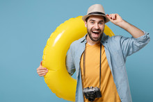 Excited Traveler Tourist Man In Summer Casual Yellow Clothes With Photo Camera Isolated On Blue Background. Passenger Traveling Abroad On Weekends. Air Flight Journey Concept. Hold Inflatable Ring.