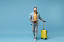 Laughing Traveler Tourist Man In Yellow Casual Clothes With Photo Camera, Suitcase Isolated On Blue Background. Male Passenger Traveling Abroad On Weekends. Air Flight Journey Concept. Looking Camera.