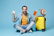 Cheerful traveler tourist man in yellow clothes isolated on blue background. Passenger traveling abroad on weekend. Air flight journey Sit near suitcase hold passport boarding pass tickets air plane.