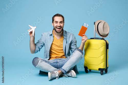 Foto Cheerful traveler tourist man in yellow clothes isolated on blue background