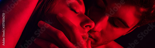 close up view of passionate young couple kissing in red light, panoramic shot Canvas-taulu