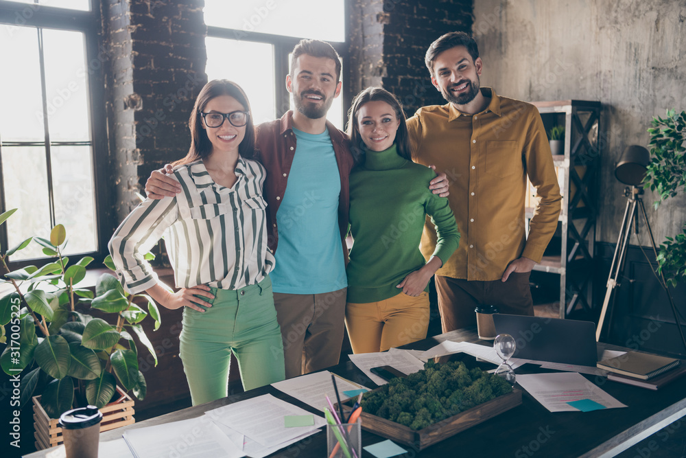 Fototapeta Company of four nice attractive friendly professional cheerful cheery people leaders partners IT specialists hugging support corporate climate at work place station office indoors