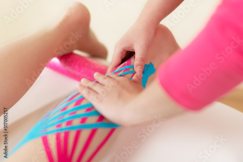 Physical therapist applying kinesio tape on female patient's calf Wallpaper Mural