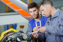 Two Mechanics Working On A Small Aircraft In A Hangar