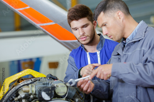 Canvas Print two mechanics working on a small aircraft in a hangar