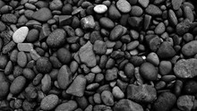 Black Pebbles On The Beach Bac...