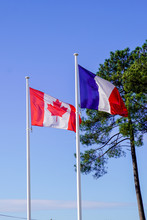 Canadian And French Flags Flyi...