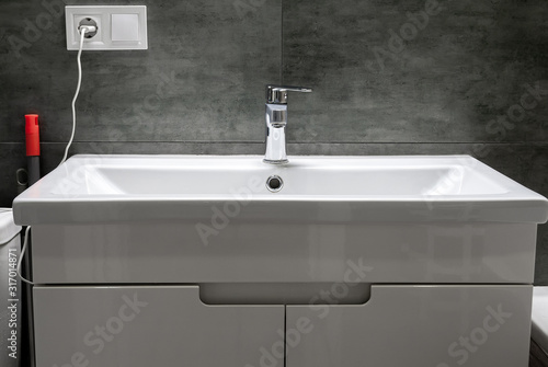 Cuadros en Lienzo Modern white rectangular sink with chromed metal faucet for hot and cold water in a stylish bathroom with gray concrete wall