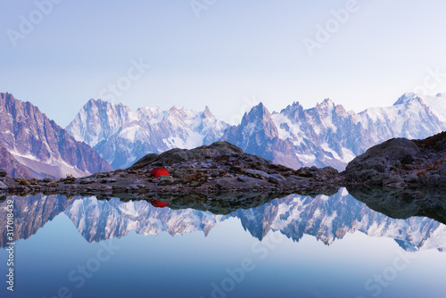 Red tent on Lac Blanc lake coast in France Alps Wallpaper Mural
