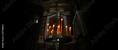Candle light in dark in Christianity church. Fototapete