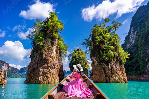 Fototapeta Beautiful girl sitting on the boat and looking to mountains in Ratchaprapha Dam at Khao Sok National Park, Surat Thani Province, Thailand. obraz na płótnie