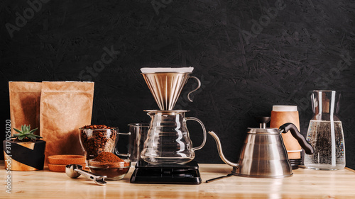 Alternative method of making coffee using a funnel filter, accessories for coffee drinks on a wooden table