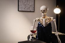 Skeleton In Dress With Wine Sitting At Table Indoors