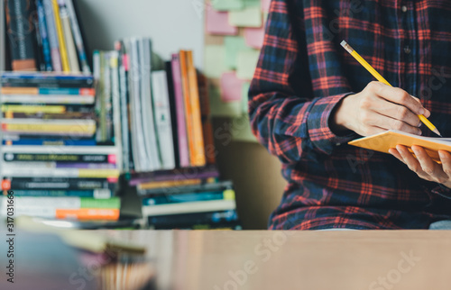 Obraz high school,university student study.hands holding pencil writing paper answer sheet.sitting lecture chair taking final exam attending in examination classroom.concept scholarship for education abroad - fototapety do salonu