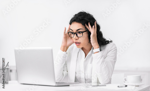 Photo Shocked surprised latin woman using pc touching temples