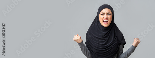 Angry emotional arabic girl screaming in fury over gray studio background Canvas Print
