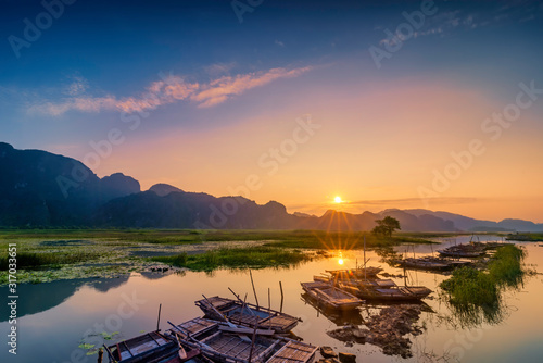 Landscape with boat in Van Long natural reserve in Ninh Binh, Vietnam Wallpaper Mural