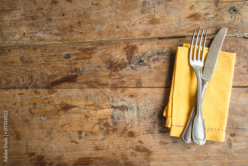 Table setting with antique fork and knife, yellow linen napkin on old wooden background Fototapet