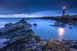 Leinwanddruck Bild - Twilight begins yielding to daylight at St. Johns Point Lighthouse. Rocky coastline with blurred water and sky, long exposure photography
