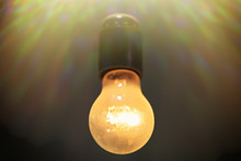 A Simple Light Bulb Lit On A Black Wire