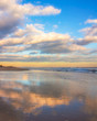 Beautiful warm golden sunlit clouds during sunset perfectly reflecting in the sand on a beach. Fire Island National Seashore - New York