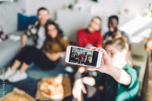 Obraz Selfie of multiethnic friends at home party on smartphone screen - fototapety do salonu