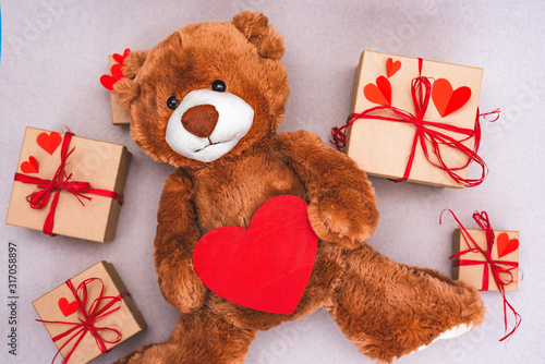 Teddy Bear with red heart and gift box. Valentines Day creative greeting card. #317058897