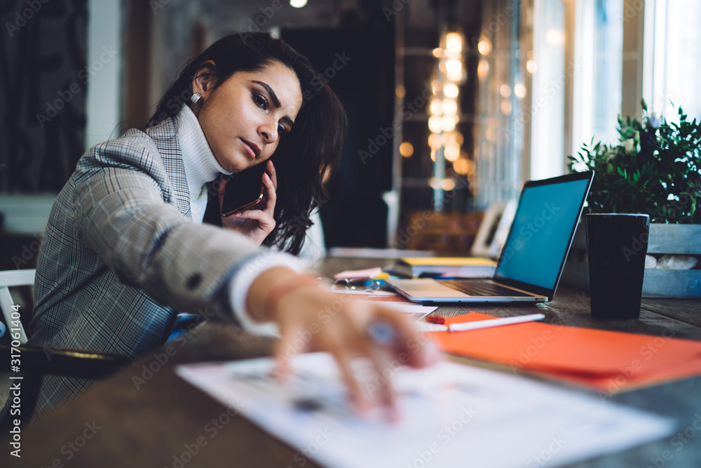 Fototapeta Serous female calling on smartphone taking document at workplace