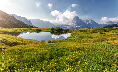 Wall mural - Beautiful alpine countryside with fairy lake. Awesome Alpine highlands in sunny day. Amazing Nature Scenery of Dolomites Alps. Great Scene in the mountains, place near Seceda peak. Val Gardena. Italy