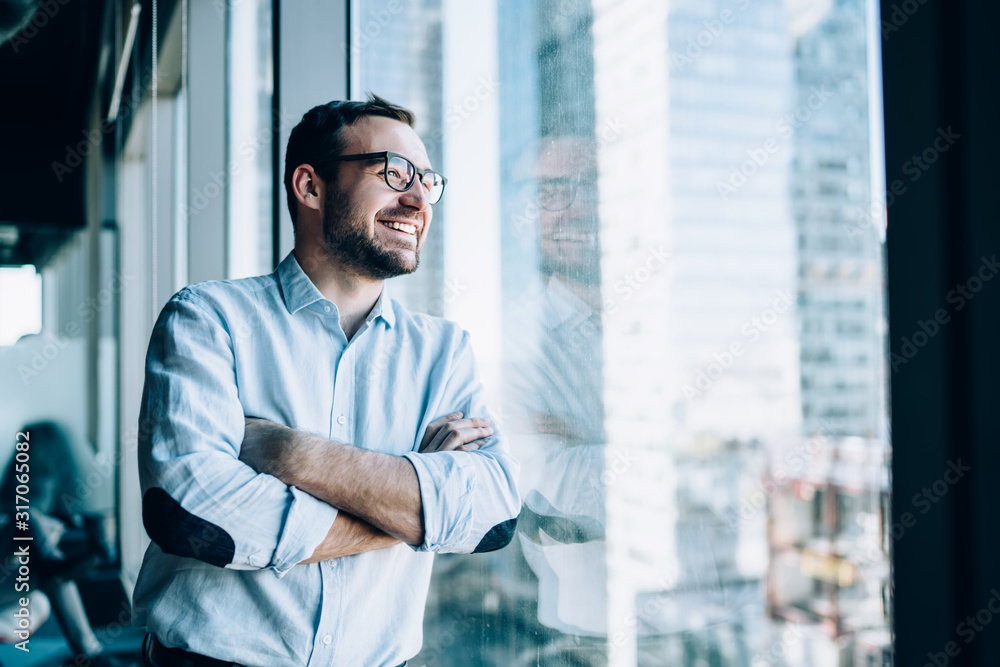 Fototapeta Cheerful male entrepreneur with crossed hands standing near office window view and smiling during work day in company, Caucasian successful corporate boss feeling good from wealthy lifestyle