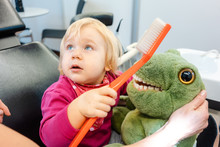 Child At The Dentist Brushing Teeth Of A Plush Toy