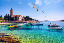 View At Amazing Archipelago With Fishing Boats In Front Of Town Hvar, Croatia. Harbor Of Old Adriatic Island Town Hvar With Seagull's Flying Over The City. Amazing Hvar City On Hvar Island, Croatia.