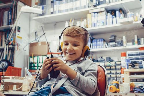 Happy kid with headphones using CB radio in a workshop. Wallpaper Mural