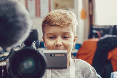 Happy kid using video camera while filming in movie studio. Canvas Print