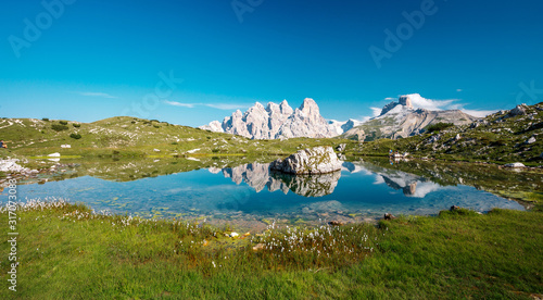 Wall mural - Impressively beautiful Fairy-tale mountain lake in Italian Alps. Breathtaking Scene. Panoramic view of beautiful mountain landscape in Alps with Lake. Incredible Dolomites Alps In Sunny Day.