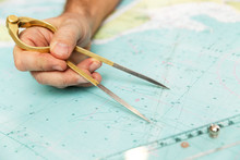 The Captain Measures The Distance On The Map With A Compass. Close-up.