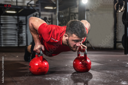 Fotografie, Obraz Young fit sweaty muscular man with big muscles doing push ups on two big old hea