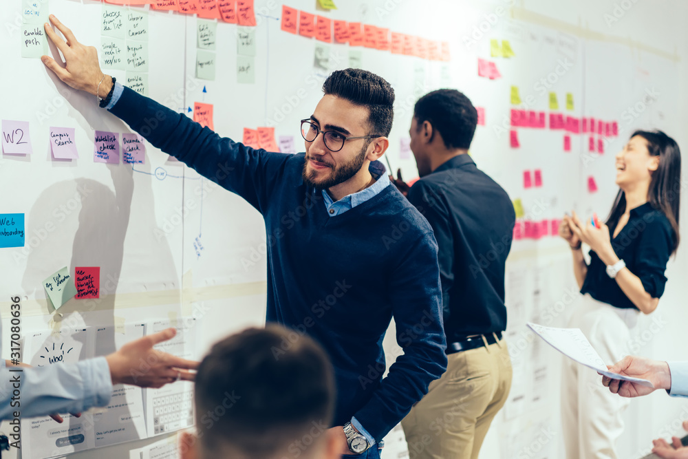 Fototapeta Smart multiethnic office employee making sticky notes on wall at office