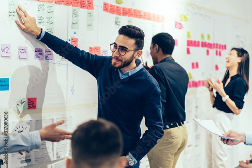 Fototapety, obrazy: Smart multiethnic office employee making sticky notes on wall at office