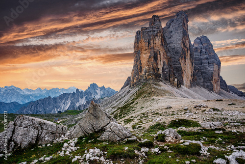 Awesome alpine highlands during sunset. Amasing nature landscape. Tre Cime di Laveredo, three spectacular mountain peaks with colorful sky, Dolomites Alps, South Tyrol, Italy. Picture of wild area.