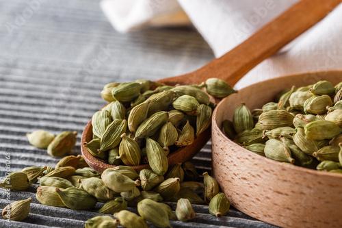 Fototapeta fragrant green cardamom on a wooden rustic background obraz