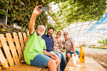 Family And Friends Have Fun All Together In Outdoor Leisure Activity Sit Down On A Recycled Wooden Bench And Taking Picture Selfie With Modern Technology Smartphone