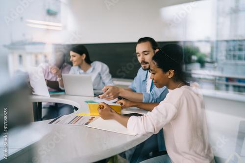 Fotografija Multiethnic coworkers sitting at table n office