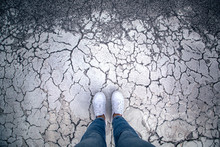 Woman Stands On Cracked Asphal...
