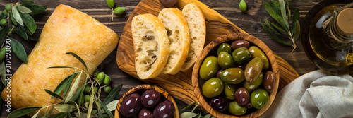 Olives, olive oil and ciabatta on wooden table. Canvas Print
