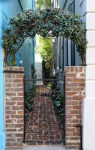 Visible From The Street, A Weathered Wrought Iron Gate Between Buildings Guards A Walkway Lined With Plants And Old Brick Pavers. The Gate Is Crowned With An Arch Of Evergreen Star Jasmine.