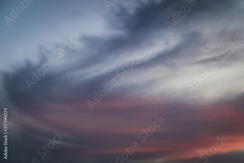 Photo Wispy orange, purple and grey clouds sit atop a darkened blue sky at sunset on t