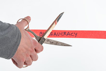 Male Hand Cutting Through Bureaucracy Red Tape With Scissors Isolated On White With A Shallow Depth Of Field And Copy Space