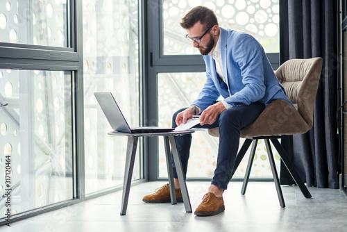 Obraz business caucasian man sitting in working with laptop in office near window - fototapety do salonu