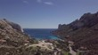 Parc National de Calanque, southern France. Beautiful teal ocean flanked by mountainous ranges. Aerial drone 4K backwards moving dolly vertical pan.